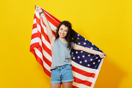 u s a: Cheerful teenage patriotic girl holding american flag of the U. S. on yellow background in studio