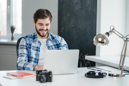 幸せな若い男のオフィスで座っていると、ラップトップ コンピューターを使用して笑みを浮かべて、オンライン チャットします。ビデオ会話を持つ