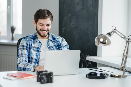 Happy young man sitting in office and using laptop computer, smiling, chatting online. Handsome man having a video conversation Standard-Bild