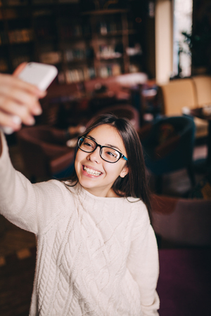 millennial: vertical shot of teenage girl in glasses taking a selfie in a cafe