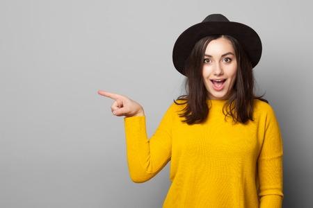 улыбается молодая женщина, указывая пальцем в сторону, изолированных на сером фоне Фото со стока