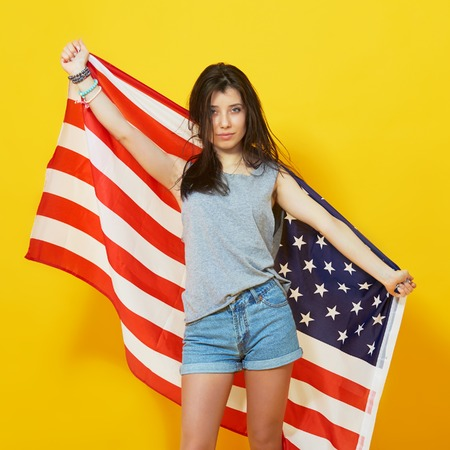 u s: Cheerful teenage patriotic girl holding american flag of the U. S. on yellow background in studio
