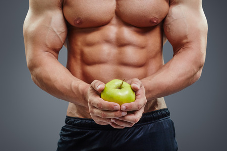 Close up of shirtless bodybuilder holding an apple in his hands. Fit man holding apple on six pack abs background. Healthy diet concept. Stock Photo