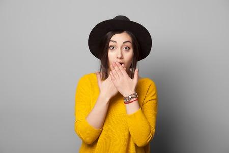 Потрясенный девушка закрывает рот руками, изолированных на сером
