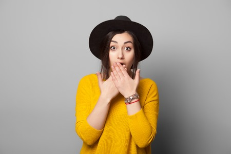Shocked girl covers her mouth with hands, isolated on grey Stockfoto