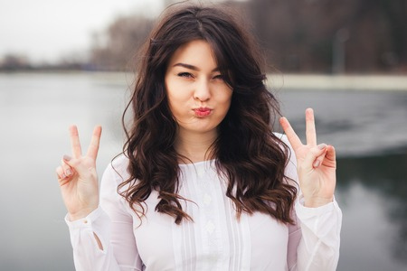 woman hairstyle: Gorgeous Young Happy Brunette Woman Wearing White Clothes and Showing Peace Sign
