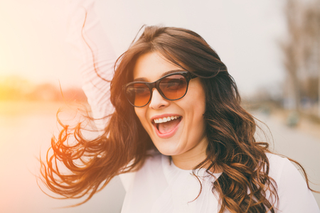 flare up: Fashion portrait of young sensual brunette woman with long amazing curled hair wearing sunglasses, natural make up. Happy girl with lens flare Stock Photo