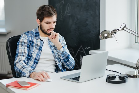 busy beard: Handsome businessman wearing casual clothes working with laptop in office. concentrated man using computer Stock Photo