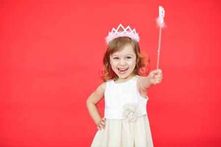Jonge fee in een witte kleding en een kroon die een toverstokje in haar hand houden die over rode achtergrond wordt geïsoleerd