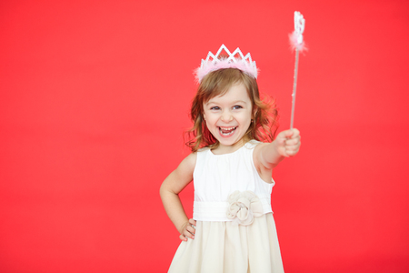 Young fairy in a white dress and crown holding a magic wand in her hand isolated over red background