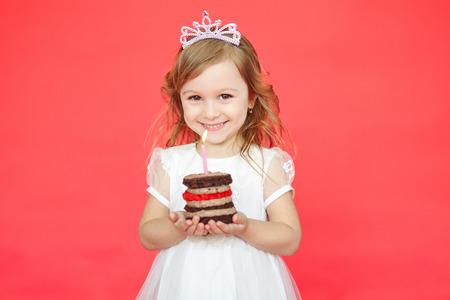 Niña con la corona que sostiene una torta de cumpleaños con velas aisladas sobre fondo rojo Foto de archivo