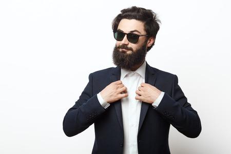 黒のビジネス スーツを着て幸せな流行に敏感な男の肖像画。ファッションは、白い背景で隔離されたポーズの男性モデル髭。