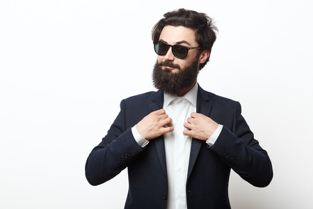 Portrait of happy hipster guy wearing a business black suit. fashion bearded male model posing isolated over white background.