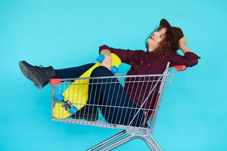 Fashion smiling hipster woman having fun wearing a hat with yellow skateboard sitting in the shopping trolley cart isolated over blue background