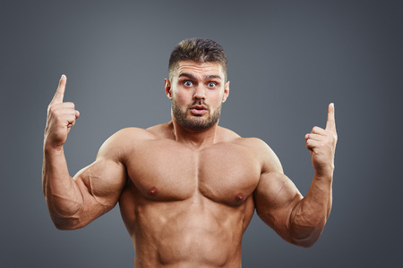 fingers on top: Shocked strong man pointing fingers upwards over grey background. Healthy bodybuilder surprised showing to the top copy space.
