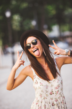 tongue out: Gorgeous Fashion Funky Girl wearing sunglasses and hat swowing tongue and peace sign outdoors on a summer day Stock Photo
