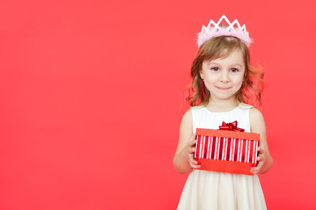 corona navidad: Cute little preschooler girl christmas portrait, isolated on red. Child girl wearing crown and white dress holding a red gift box  isolated over red background Foto de archivo
