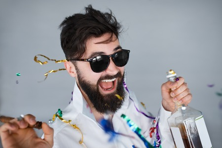 Bearded man with sunglasses holding a bottle of alcohol and cigar at celebration. Ecstatic portrait of drunk man having fun at wild party