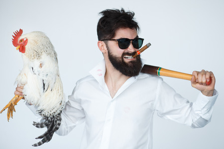 crazy guy: Crazy guy in rage holding a cock and baseball bat. Confident angry man in sunglasses smoking cigar. Stock Photo