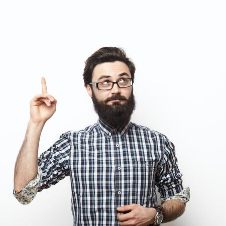 Uomo casuale che la ricerca e puntando il dito a uno spazio vuoto su sfondo bianco. Ho un concetto di idea
