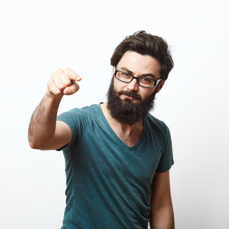 portrait of a angry young man with beard and glasses wearing t-shirt pointing to camera. We need you concept Stockfoto
