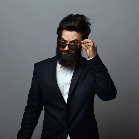 only 1 man: handsome young man adjusting his sunglasses while standing against grey background. Confident bearded man wearing white shirt and black suit looking angry to camera.