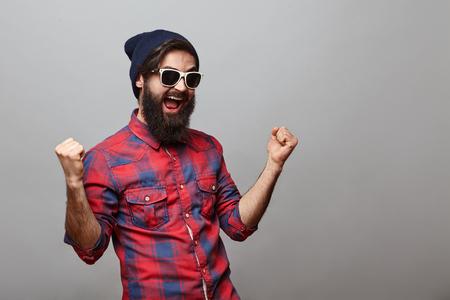 Gelukkige jonge hipstermens die over grijze achtergrond wordt geïsoleerd. Bebaarde man met bril en hoed doet alsof hij iets gewonnen heeft met kopie ruimte
