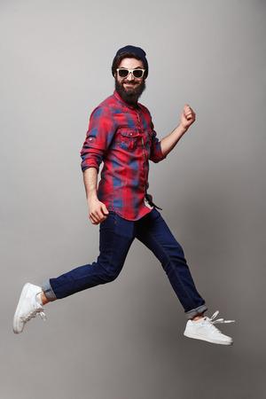 Feliz excitado e jovem homem barbudo. Retrato engraçado no modelo masculino casual novo no salto cómico no fundo cinzento.