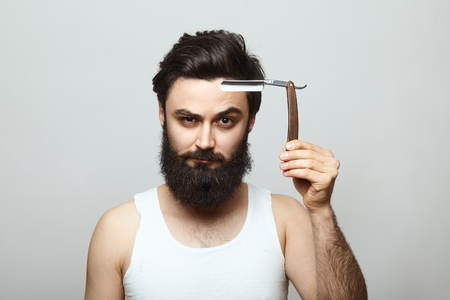 accesory: Young man with beard holding a barber shop accesory - old-fashioned razor. Hipster shaving concept Stock Photo