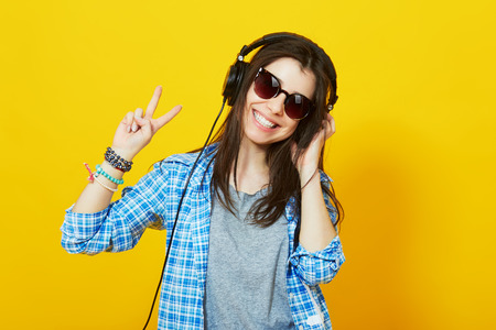 millennial: Modern happy millennial teenage girl with sunglasses, headphones smiling showing peace gesture over yellow background, vibrant colors. Stock Photo