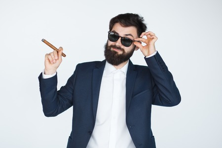 Bearded guy in sunglasses smoking cigar on white background. Confident businessman with beard in black suit holding a cigar.