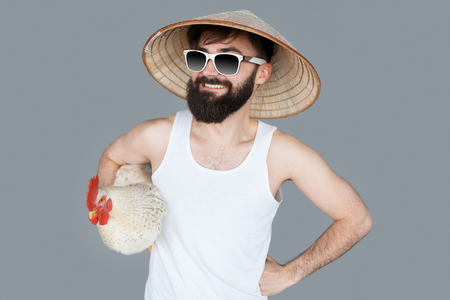 conical hat: Bearded tourist man going to Asian countries with asian conical hat and white cock. Crazy ready to travel concept.