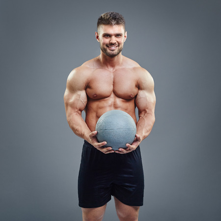 accesories: Smiling muscular man holding a medicine fitness ball on grey background. Strong bodybuilder presenting gym training accesories.
