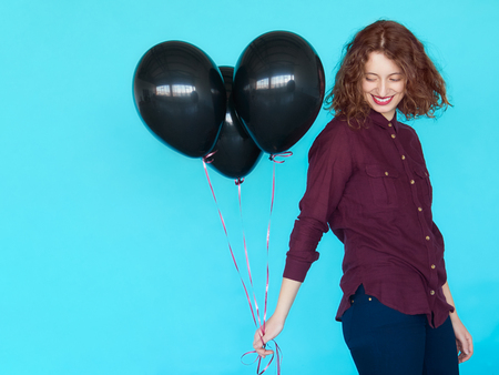 Portrait of cheerful fashion hipster girl with caucasian appearance, standing over blue color wall and holding a bunch of black balloons Stock Photo