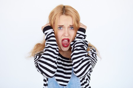 woman prison: Beautiful young woman prisoner isolated on a white background. Shocked blonde girl wearing striped prison clothes screaming Stock Photo