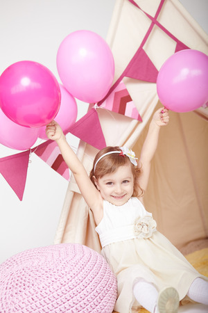 Vertical portrait of happy cute little girl rejoicing at birthday party. Kid girl in white dress with pink decorations holding hands raised and smiling