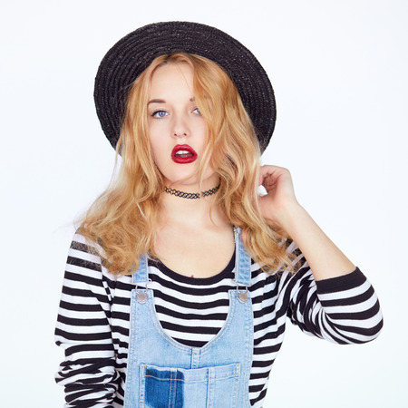 youthfulness: Portrait of happy hipster girl with blond hair and red lips wearing fashion clothes and black hat over white background. Closeup face portrait of teenage girl in studio Stock Photo