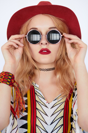 artsy: Closeup face portrait of beautiful hippie young woman wearing boho chic clothes, red hat and sunglasses on white background. Artsy bohemian style.