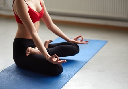 legged: Unrecognizable young woman does yoga on mat indoors. Cropped portrait of girl sitting in seated cross legged pose relaxing in zen. Stock Photo