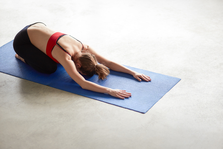 ushtrasana: Balasana. Beautiful yoga woman practice in a training hall background. Yoga concept. Stock Photo