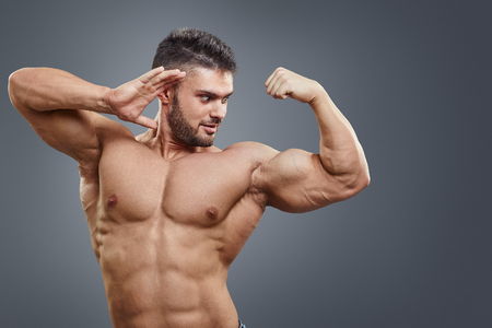 strong growth: Human Muscle Bicep Growth concept. Strong man surprised of his muscular arm isolated on grey background. Stock Photo