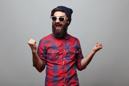 happy hipster man with beard wearing red checkered shirt and sunglasses exults isolated on grey background