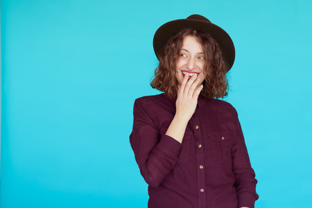 turqoise: Surprised young woman wearing warm violet shirt and stylish hat over blue turqoise color background with copy space. Excited hipster girl covering her mouth looking to copyspace.