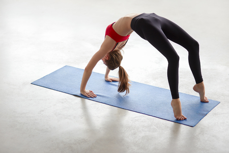 Beautiful young woman working out in loft interior, doing yoga exercise on blue mat, stretching, standing in Bridge Pose, Urdhva Dhanurasana Upward Bow, Chakrasana Wheel Posture, full length