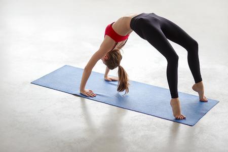 Beautiful young woman working out in loft interior, doing yoga exercise on blue mat, stretching, standing in Bridge Pose, Urdhva Dhanurasana Upward Bow, Chakrasana Wheel Posture, full length
