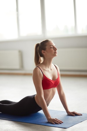Vertical portrait of one woman exercising sun salutation cobra pose yoga posture in studio with big windows and natural light. Girl doing aerobic exercise for back pain relief