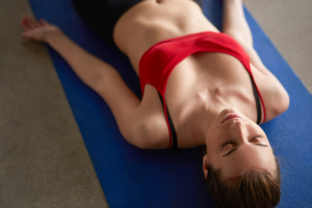 body posture: Beautiful happy young woman in bright sportswear lying down indoors on blue mat. Girl staying in Shavasana Corpse or Dead Body Posture, resting after practice, meditating, breathing Stock Photo
