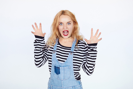 pussycat: Portrait of blond girl acting like pussycat alluring over white background. Teenage girl scares you