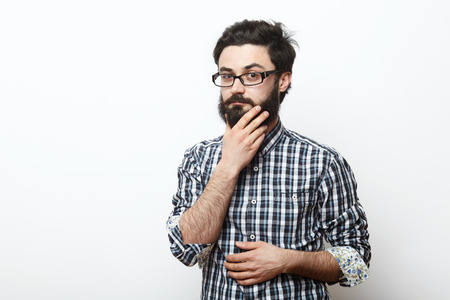 hesitation: man in glasses touching his beard and thinking over white background. Hesitation and doubt concept Stock Photo