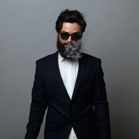 hitman: Mysterious man with beard and shades wearing black suit and smoking over dark background